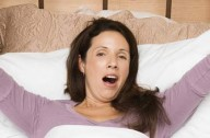 A woman yawning in bed