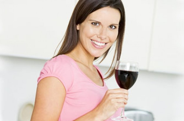 Woman holding glass of red wine_Photolibrary