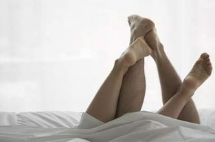 Couples legs in bed_photolibrary
