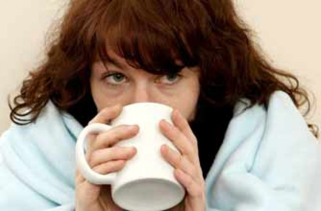 Woman with common cold drinking a hot drink_REX