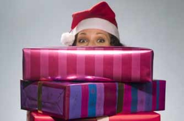 Woman holding a pile of Christmas gifts_rex