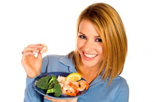 Woman eating prawns and broccoli