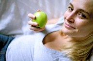 Pregnant woman eating an apple using the health in pregnancy grant