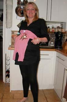 Anna at 39 weeks pregnant holding a babygro up against her bump