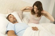 Woman in bed with a man who's snoring