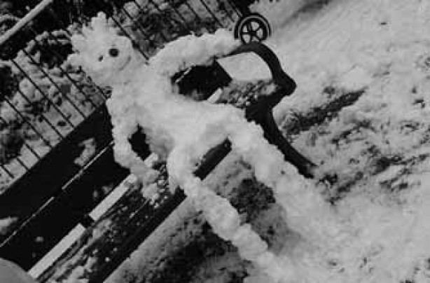 A snow man sitting on a bench!