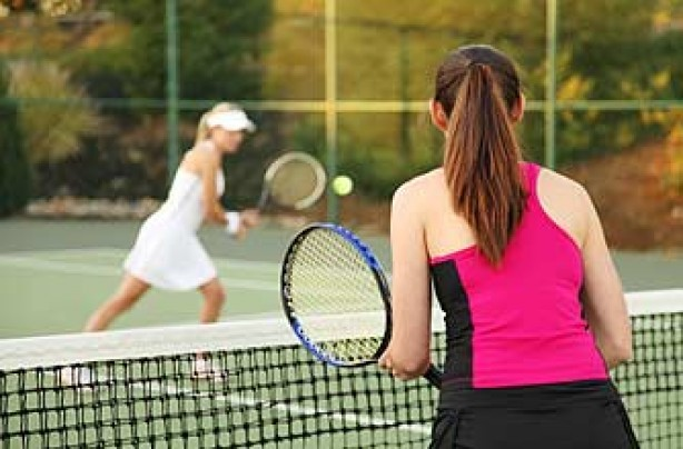 women playing tennis together