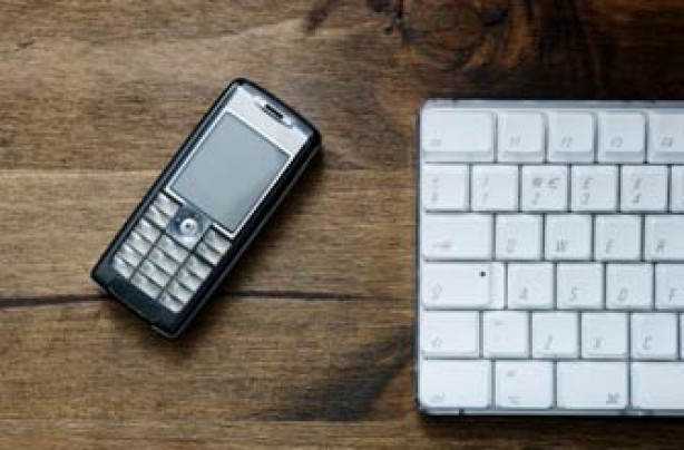 mobile phone and a keyboard on a desk