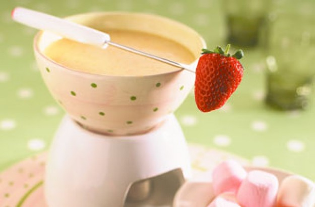 Marshmallows and strawberries fondue in white chocolate