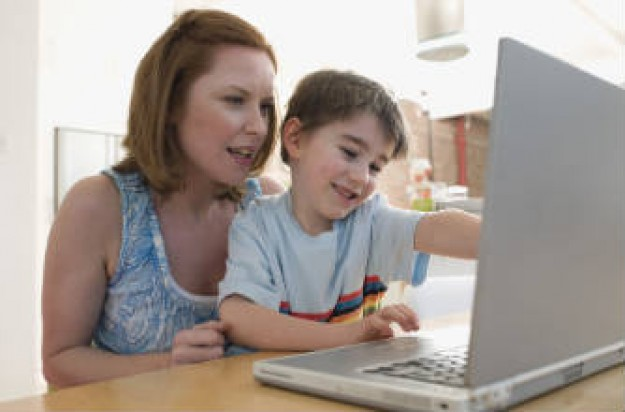 Mum helping her son on the computer