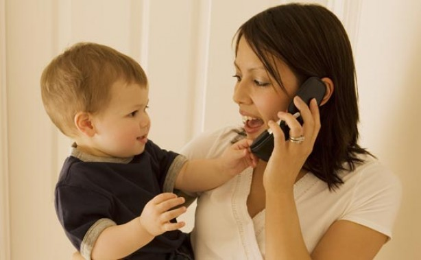 Mum talking on the phone while holding her son