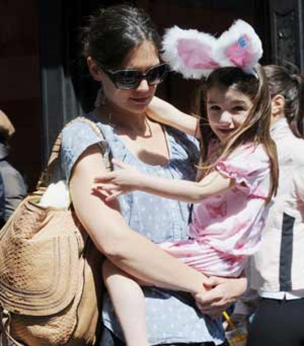 Suri wears big pink rabbit ears while being carried by mum