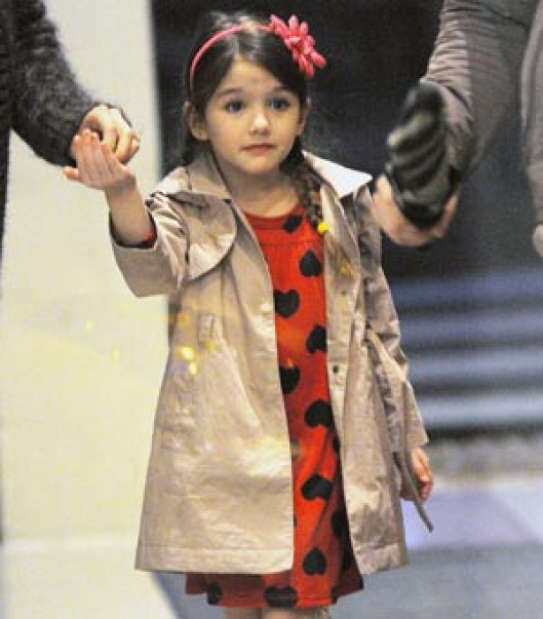 Suri wearing a red dress with black polka dots