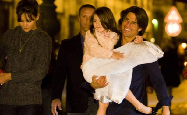 Suri Cruise being carried by her dad