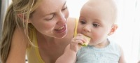 Family, babies, weaning baby girl eating an apple