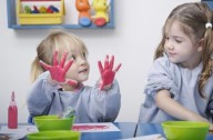 Girls finger painting at nursery