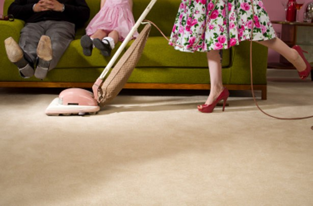 Woman hoovering under husband's feet
