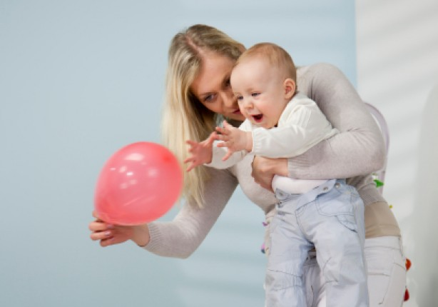 Mother and baby playing with a red balloon
