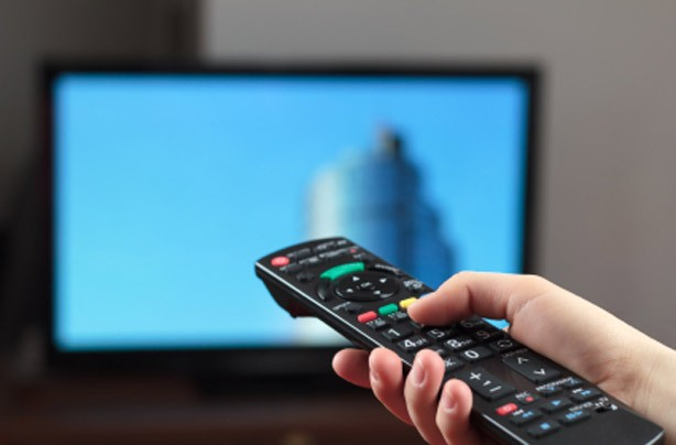 Woman pointing the remote at a TV