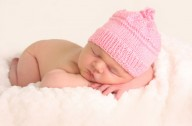 Newborn baby with a pink hat on