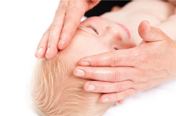 Massage baby's head and face