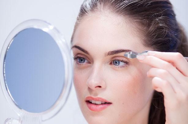 woman plucking eyebrows photo