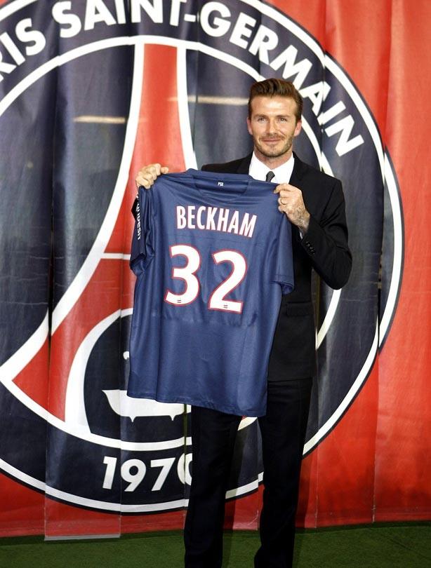 David Beckham holds his new shirt for Paris Saint Germain