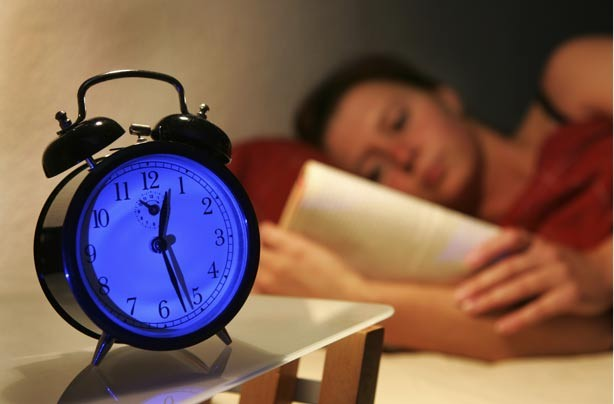 Woman in bed reading next to alarm clock
