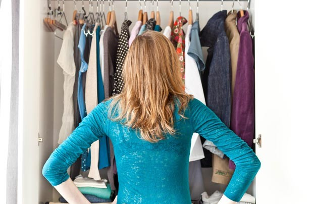 Woman looking into a wardrobe full of clothes