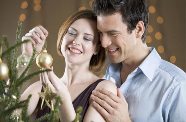 Couple putting decorations on Christmas tree