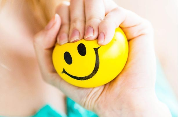 Woman holding smiley face stress ball