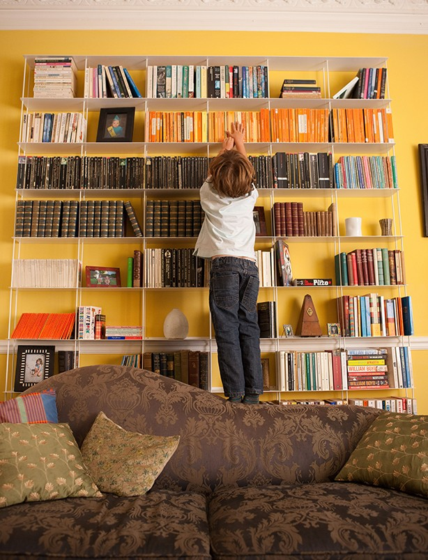 Boy climbing bookshelf