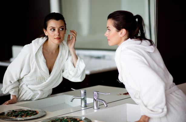 Woman in dressing gown looking in mirror