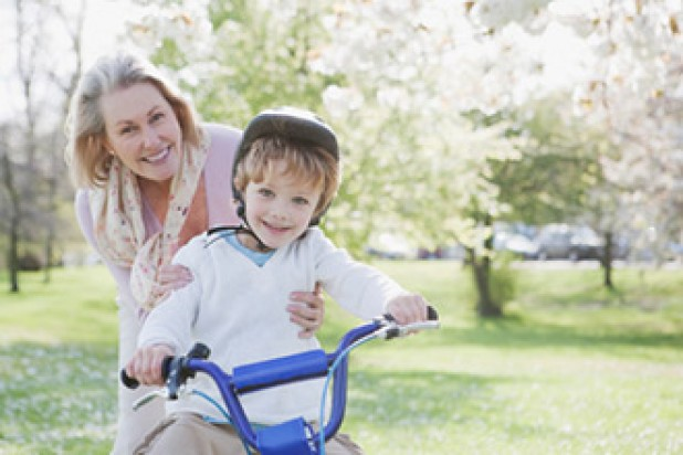 A toddler riding a bike with his grandmother helping him