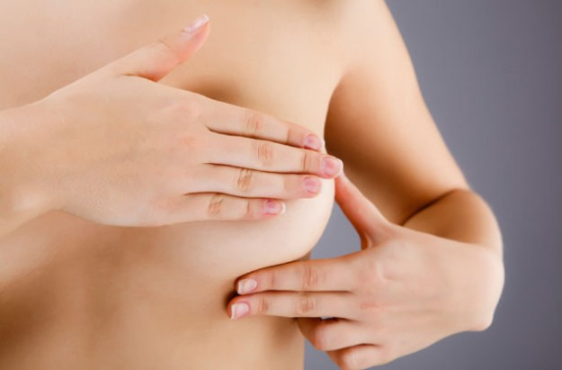 Woman examining her breasts, breast cancer