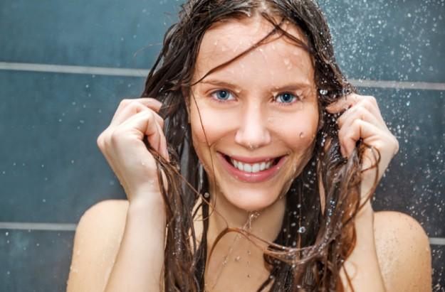 Woman in shower, how often should you wash your hair