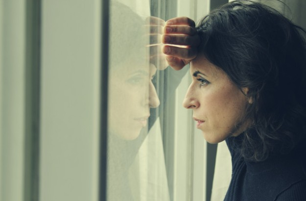 Woman looking out of a window, stress