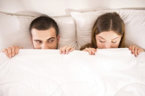 Woman and men in bed, asleep, sleep problems