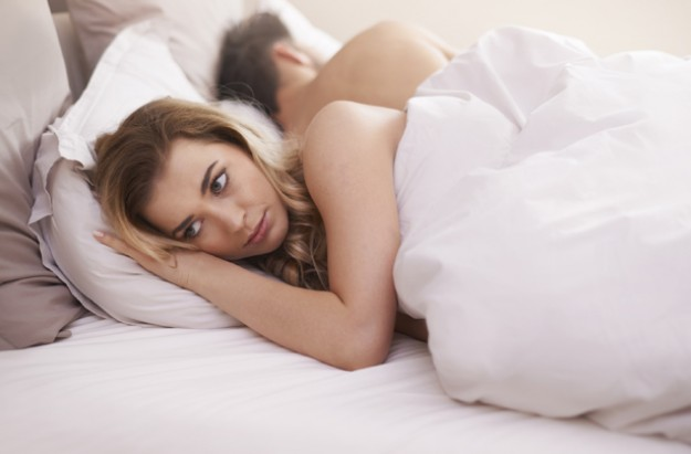 Couple lying in bed, infertility