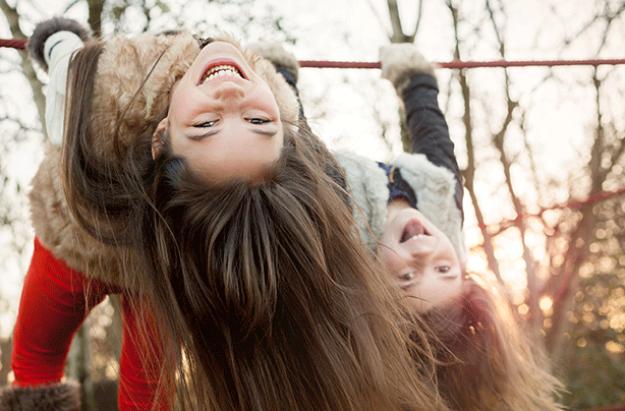 Girls swinging on playground, child development stages