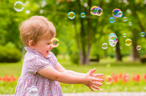Girl playing with bubbles, baby games